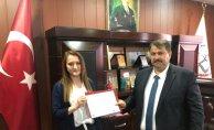 Ulusal Kalite Etiketi Almaya Hak Kazanan Öğretmenin Ödülü Turan'ın Elinden